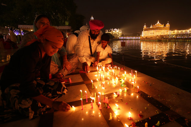 Devotees light candles at the specially illuminated Golden Temple, the holiest of Sikh's religious sites in the pre-dawn hours on the occasion of the 485th birth anniversary of the fourth Guru or the master of the Sikhs Sri Guru Ramdas Ji in Amritsar, India, 15 October 2019. Sri Guru Ramdas Ji also established the city of Amritsar. The birth anniversary of the fourth Sikh Guru is one of the major religious events for Sikh community, especially for the people of Amritsar. (Photo by Raminder Pal Singh/EPA/EFE)