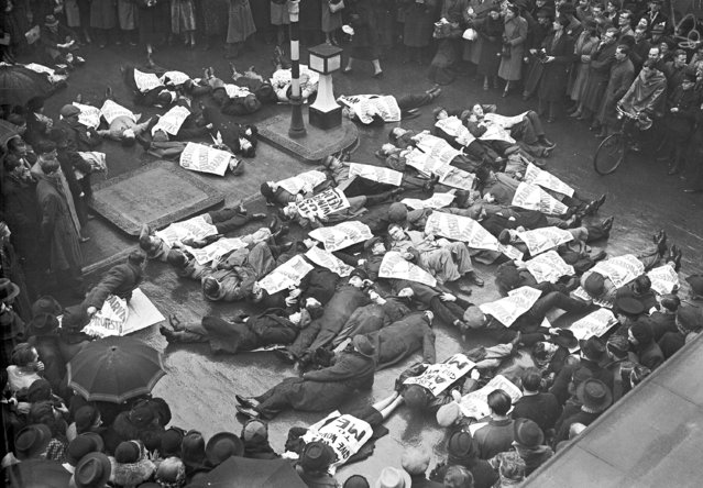 Large numbers of unemployed people, carrying posters drawing attention to their for winter relief, lay down in Oxford Street, London, January 17, 1939, stopping all the traffic. (Photo by AP Photo)