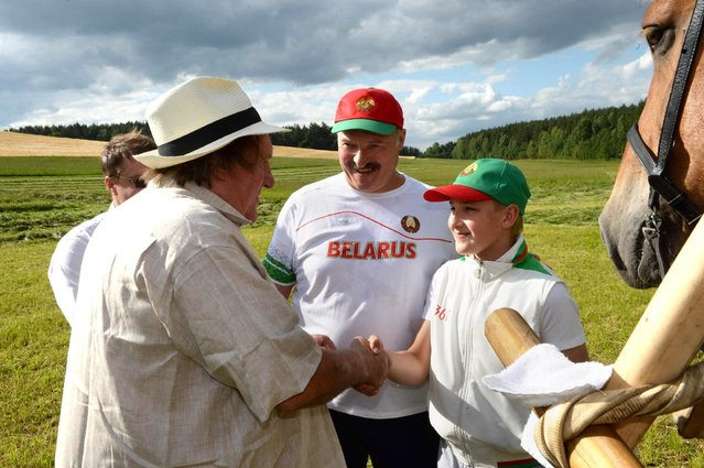 In this photo taken Wednesday, July 22, 2015, Belarus' President Alexander Lukashenko, center, looks on as his son Nikolai, left, and French actor Gerard Depardieu shake hands in the presidential residence of Ozerny, outside Minsk, Belarus. (Photo by Andrei Stasevich/BelTA Photo via AP Photo)