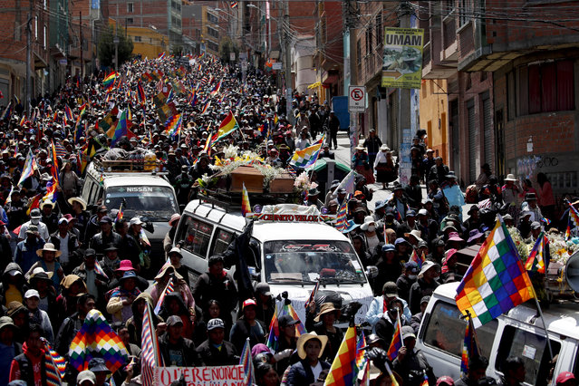 Anti-government demonstrators accompany the coffins that contain the remains of people killed in clashes between supporters of former President Evo Morales and security forces, in a funeral procession into La Paz, Bolivia, Thursday, November 21, 2019. At least eight people were killed Tuesday when security forces cleared a blockade of a fuel plant by supporters of former President Evo Morales at protesters in the city of El Alto. (Photo by Natacha Pisarenko/AP Photo)