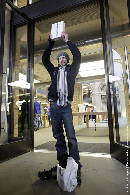 Craig Jobbins, first buyer of the new iPad to leave the Apple Store, poses for photographers in Covent Garden on March 16, 2012 in London