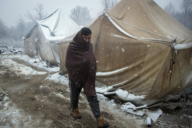 A migrant walks amid tents during snowfall at the Vucjak refugee camp outside Bihac, northwestern Bosnia, Monday, December 2, 2019. Despite calls for their relocation before winter, hundreds of migrants remain stuck in a make-shift tent camp in northwestern Bosnia as a spate of snowy and cold weather hit the region. (Photo by Darko Bandic/AP Photo)