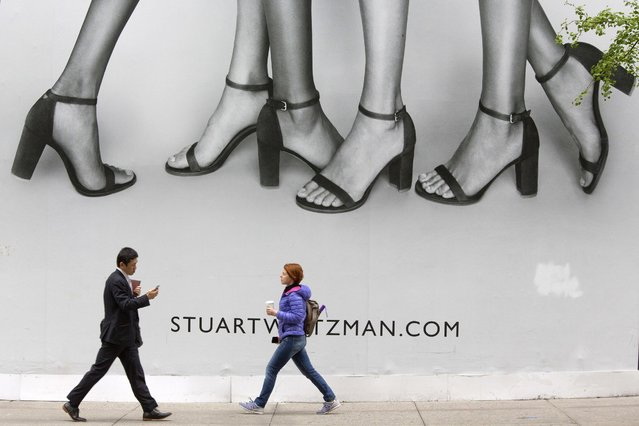 Pedestrians walk past a giant billboard on display on 5th Avenue in Midtown Manhattan, Wednesday, May 4, 2016 in New York. (Photo by Mary Altaffer/AP Photo)