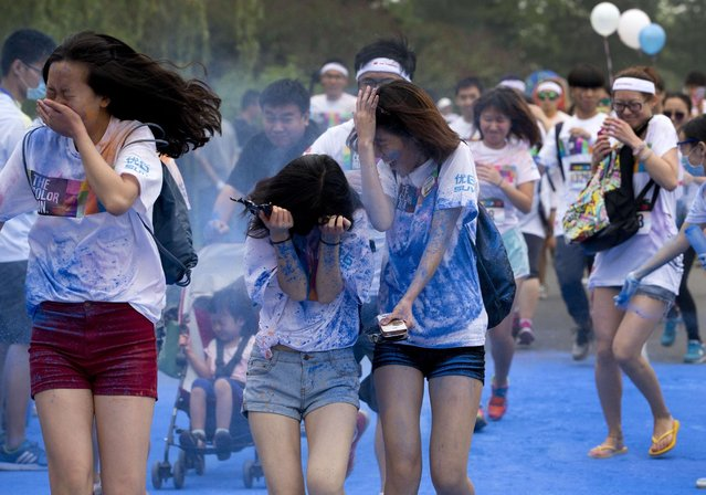 "Participants try to cover themselves from color powder sprayed by volunteers as they run through a ""color station"" during a five-kilometer color run event held in Beijing, China Saturday, June 21, 2014. (Photo by Andy Wong/AP Photo)"