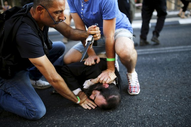 People disarm an Orthodox Jewish assailant after he stabbed and injured six participants at an annual gay pride parade in Jerusalem on Thursday, police and witnesses said July 30, 2015. (Photo by Amir Cohen/Reuters)
