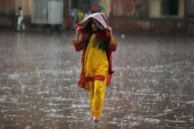 A Pakistani girl covers her head with a prayer mat to shelter from rain as she goes to offer Eid al-Fitr prayers at the historical Badshahi mosque in Lahore, Pakistan, Saturday, July 18, 2015. (Photo by K. M. Chaudary/AP Photo)