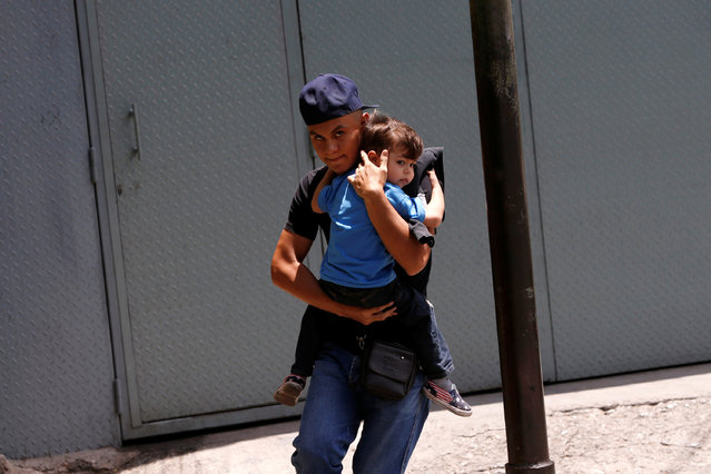 A man carrying a child runs away during clashes between Venezuelan protesters and riot police during a demonstration over food shortage and against Venezuelan President Nicolas Maduro's government in Caracas, Venezuela, June 10, 2016. (Photo by Carlos Garcia Rawlins/Reuters)