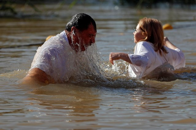 Pilgrims take a dip in the waters of the Jordan River during a baptism ceremony at the Qasr el-Yahud site, near Jericho, in the Israeli-occupied West Bank, January 6, 2020. (Photo by Mohamad Torokman/Reuters)
