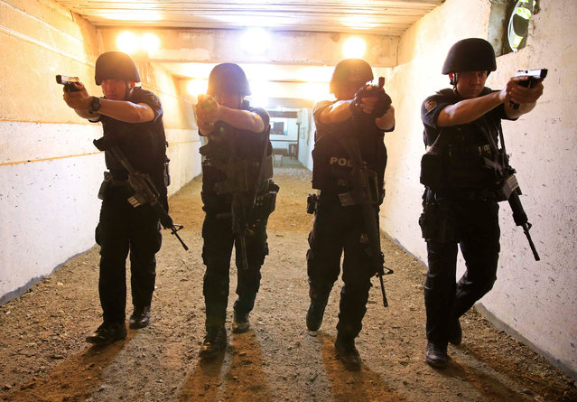 Members of the Philippine National Police Special Reactions Unit aims their pistols at a target range during an agility test inside a police station in metro Manila, Philippines May 21, 2016. (Photo by Romeo Ranoco/Reuters)