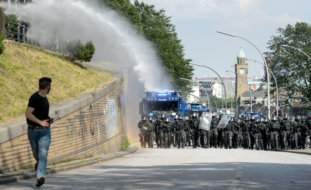 An anti G20 Summit demonstrator runs away from a police water cannon near Hamburg on July 7, 2017 in Hamburg, Germany. Leaders of the G20 group of nations are arriving in Hamburg today for the July 7-8 economic summit and authorities are bracing for large-scale and disruptive protest efforts. (Photo by Thomas Lohnes/Getty Images)