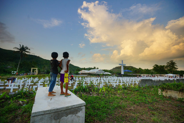Two young residents watch as people visit the mass graveyard for victims of super Typhoon Haiyan, in Tacloban City, Leyte province, central Philippines on November 8, 2019. Typhoon Haiyan struck in the predawn darkness of November 8, 2013 as the then strongest typhoon to ever hit land, leaving more than 7,360 people dead or missing across the central Philippines. (Photo by Bobby Alota/AFP Photo)