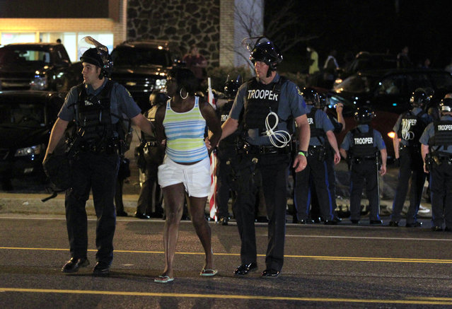 Officers arrest a protester, Monday, August 10, 2015, in Ferguson, Mo. (Photo by Jeff Roberson/AP Photo)