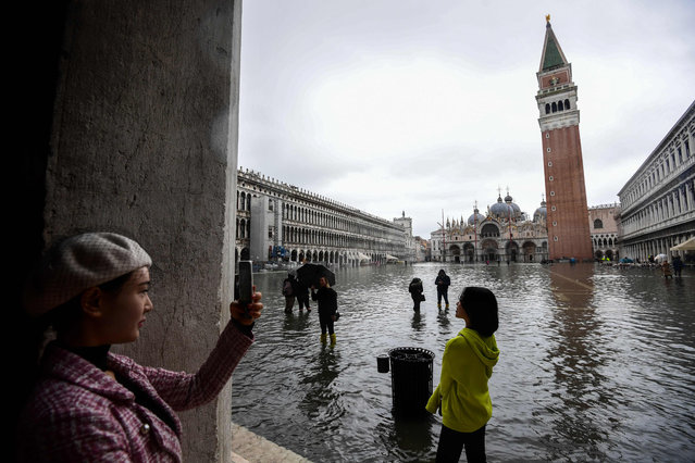 """Tourists take photos on the flooded St. Mark's Square, by the Bell Tower (Rear R) and St. Mark's Basilica (Rear C) on November 24, 2019 in Venice during a high tide """"Acqua Alta"""" meteorological phenomenon with a high of 140 cm expected. Flood-hit Venice was bracing for another, though smaller, high tide on November 24, after Italy declared on November 15 a state of emergency for the UNESCO city where perilous deluges have caused millions of euros worth of damage. (Photo by Miguel Medina/AFP Photo)"""