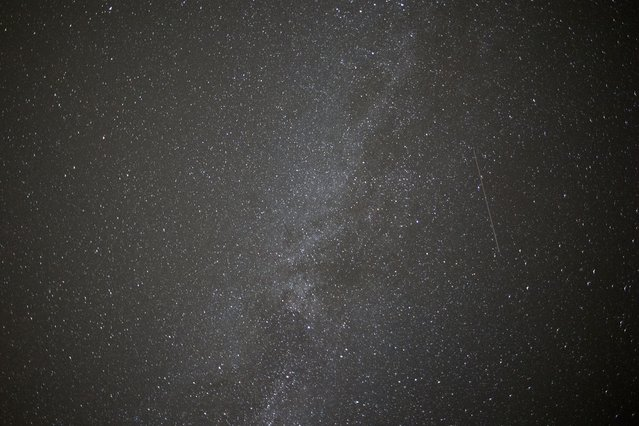 A meteor passes across the sky during the peak in activity of the annual Perseids meteor shower in the village of Rufforth, near York, northern England on August 12, 2015. The Perseids meteor shower occurs every year when the Earth passes through the cloud of debris left by Comet Swift-Tuttle. (Photo by Oli Scarff/AFP Photo)