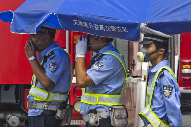 Chinese traffic police wear masks as they man a security checkpoint near the site of an explosion in northeastern China's Tianjin municipality Saturday, August 15, 2015. (Photo by Ng Han Guan/AP Photo)