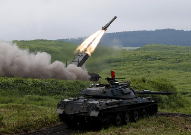 A Japanese Ground Self-Defense Force Type 92 Mine sweeping vehicle fires a rocket behind a Type 74 armoured tank during an annual training session, which is based on a scenario to defend or retake islands in Japanese territory, near Mount Fuji at Higashifuji training field in Gotemba, west of Tokyo, August 18, 2015. (Photo by Yuya Shino/Reuters)