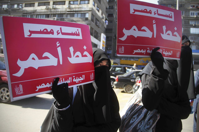 """In this December 27, 2011, file photo, two women hold up banners in Arabic that read: """"Egyptian women, red line"""", during a rally supporting women's right in Cairo, Egypt. The prosecution of a 15-year-old girl who killed a bus driver after he allegedly tried to rape her in July 2019 has reignited debate over the treatment of women in Egypt's legal system, including blaming female victims of sexual violence and the practice of administering virginity tests. (Photo by Ahmed Ali/AP Photo/File)"""