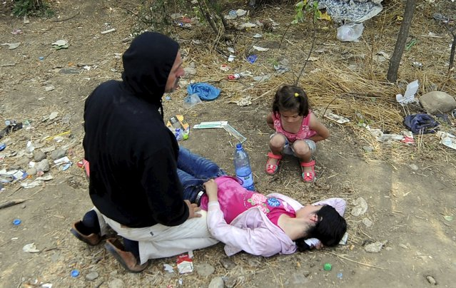 A man kneels next to his collapsed wife at the border line dividing Macedonia and Greece August 21, 2015. (Photo by Ognen Teofilovski/Reuters)