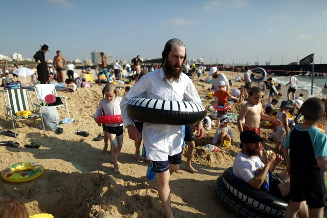 Ultra Orthodox Jews  enjoying summer time at the beach  with their families in the southern city of Ashdod, Israel, on 13 August 2014. Many Israelis are making the most of the 72-hour truce ceasefire and try to return to normal life. (Photo by Abir Sultan/EPA)