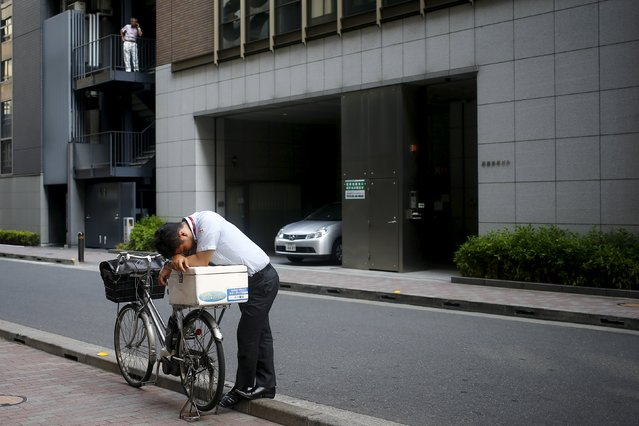 A businessman rests his head on a bike in the central district of Ginza in Tokyo, August 3, 2015. (Photo by Thomas Peter/Reuters)