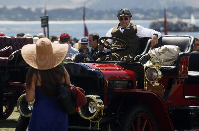 A contestant sits in his 1907 White Model G Runabout Prototype during the Concours d'Elegance at the Pebble Beach Golf Links in Pebble Beach, California, August 17, 2014. (Photo by Michael Fiala/Reuters)