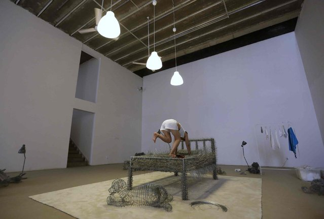 "Chinese artist Zhou Jie climbs onto an unfinished iron wire bed, one of her sculpture works, to take a nap after lunch at Beijing Now Art Gallery, in Beijing August 11, 2014. Zhou started her art project titled ""36 Days"" on August 9, in which she would live inside an exhibition hall with an unfinished iron wire bed, some iron wire sculptures in the shape of stuffed animal dolls, a certain amount of food and her mobile phone, for 36 days. (Photo by Jason Lee/Reuters)"