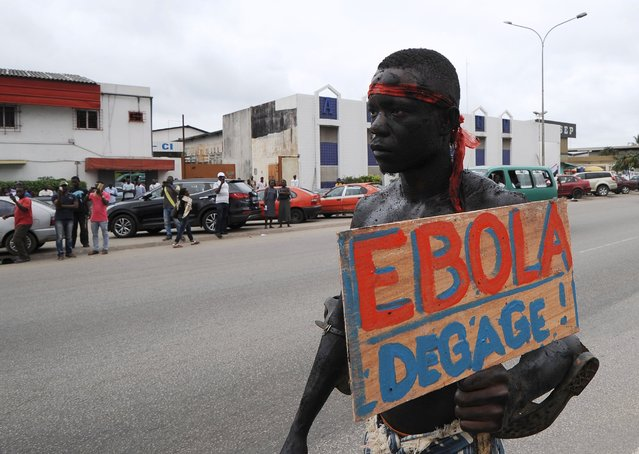 "A man holds a placard reading ""Ebola, go away!"" as members of the artist group ""'Be Kok Spirit"" march to raise awareness on the Ebola virus, on August 19, 2014 in Abidjian. The Ivory Coast announced on August 11 that it has banned all flights from countries hit by Ebola as part of steps to prevent the deadly virus from reaching the west African nation. (Photo by Sia Kambou/AFP Photo)"