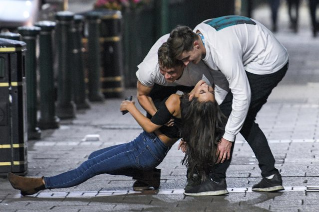 Drunk fresher is helped by students as she falls to the ground on night out at during the alcohol-fuelled Freshers' Week in Birmingham, United Kingdom on September 18, 2017. Freshers are inducted during Freshers' Week – the first week of the Academic year – one of the busiest and most fun weeks of the year. (Photo by Caters News Agency)