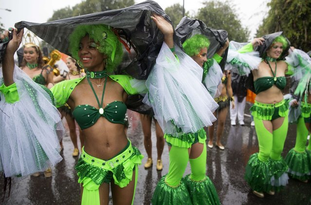 Performers shelter themselves from the rain during the Notting Hill Carnival in west London August 25, 2014. (Photo by Neil Hall/Reuters)