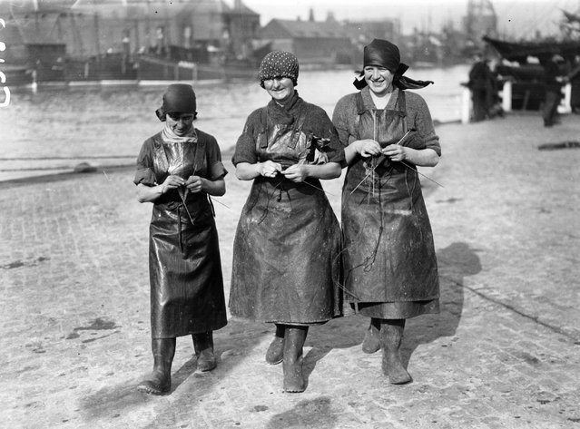 Three Scottish herring girls knitting whilst waiting for the arrival of the fishing fleet at Great Yarmouth in England, 1929. Thousands of women travel from Scotland to Great Yarmouth to process the catch during the autumn herring season. (Photo by Topical Press Agency)