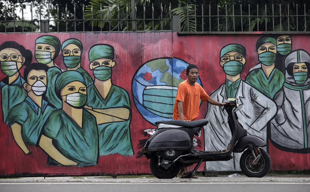 A motorists stops near a mural painted as a tribute to medical workers in Depok, on the outskirts of Jakarta, Indonesia, Wednesday, April 15, 2020. Indonesia's capital kicked off a stricter restriction to slow the spread of the new coronavirus last week as the metropolitan area has become Indonesia's coronavirus epicenter. (Photo by Dita Alangkara/AP Photo)