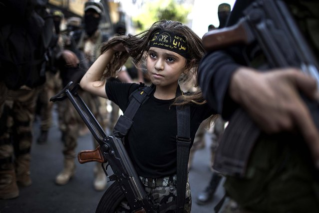 A girl holds a rifle as fighters of Al-Quds brigades, the military wing of Islamic Jihad, gather in Gaza City, on August 29, 2014. Only time will tell whether Israel will maintain the quiet it sought during 50 days of war with Palestinian militants in the Gaza Strip, and whether Hamas will leverage the world's outrage over civilian casualties to improve the lives of the coastal enclave's 1.7 million residents. (Photo by Wissam Nassar/The New York Times)