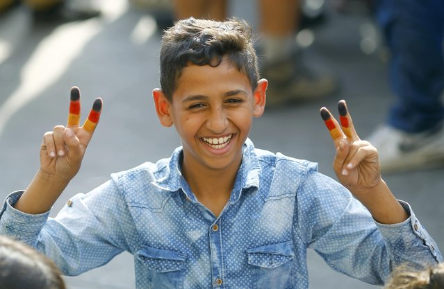 A young migrant boy with his fingers painted in the colours of the German national flag, smiles outside Keleti train station in Budapest, Hungary, September 3, 2015. (Photo by Leonhard Foeger/Reuters)