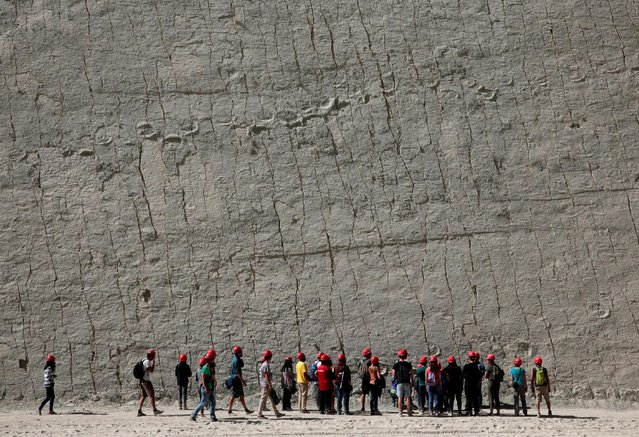 Visitors look at dinosaur footprints while visiting the Cal Orcko cliff in Cal Orcko, on the outskirts of Sucre, Bolivia, July 22, 2016. (Photo by David Mercado/Reuters)