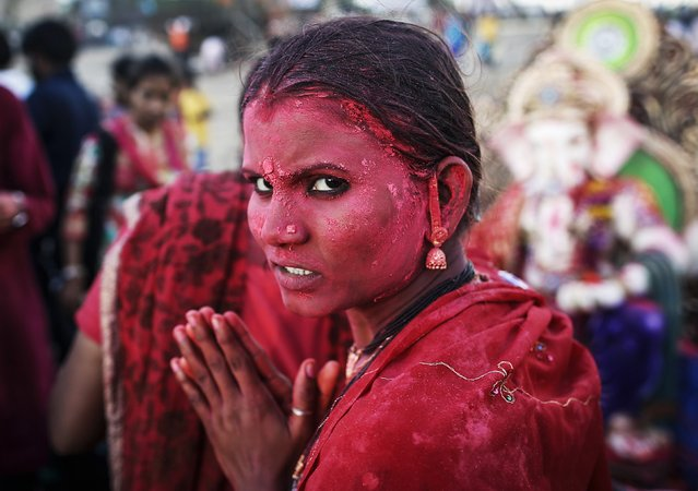 A devotee daubed in coloured powder prays as she takes part in the immersion of the idols of the Hindu god Ganesh, the deity of prosperity on the fifth day of the ten-day-long Ganesh Chaturthi festival in Mumbai September 2, 2014. Ganesh idols are taken through the streets in a procession accompanied by dancing and singing, and later immersed in a river or the sea, symbolising a ritual seeing-off of his journey towards his abode, taking away with him the misfortunes of all mankind. (Photo by Danish Siddiqui/Reuters)