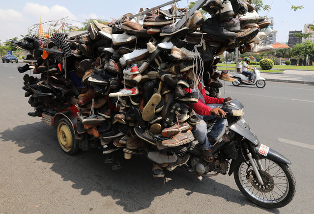 A Cambodian man sells shoes on a motorized cart travelling along a street in Phnom Penh, Cambodia, 30 April 2020. Cambodian authorities are enforcing strict traffic rules in an effort to cut down traffic accidents on the road as a new land traffic law will go into effect in the beggining of of May 2020. (Photo by Mak Remissa/EPA/EFE)