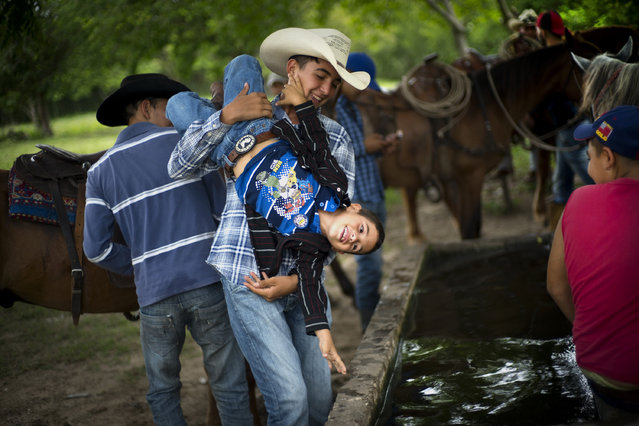 In this July 29, 2016 photo, a cowboy playfully threatens to dunk a younger boy into a water troff, during an improvised rodeo event at a farm in Sancti Spiritus, central Cuba. In the flat grasslands in the central province of Sancti Spiritus, a group of neighboring cattle ranchers founded a non-governmental organization called Future Ranchers more than a decade ago to revive Cuba's rodeo culture, which dates back centuries to Spanish colonial times. (Photo by Ramon Espinosa/AP Photo)