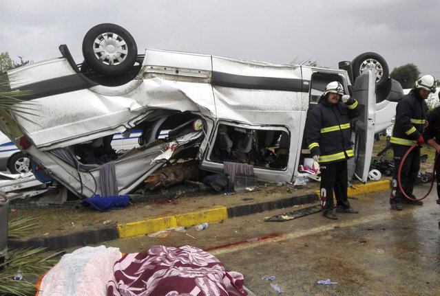 Turkish firefighters work at a scene of a traffic accident near the Mediterranean coast city of Antalya, southern Turkey, Saturday, October 7, 2017. Turkey's official news agency said a tourist bus tipped over Saturday after hitting a palm tree on a traffic island in the popular tourist destination, killing three Germans. (Photo by Mithat Abakan/DHA-Depo Photos via AP Photo)