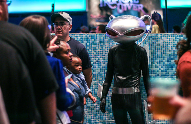 In this Saturday, September 5, 2015, photo, a man in costume looks on at fellow attendees of a private party held at the Georgia Aquarium as part of Dragon Con in Atlanta. (Photo by Ron Harris/AP Photo)