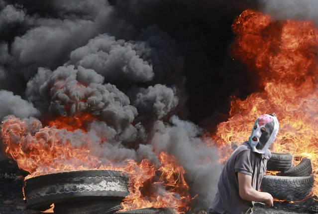 A Palestinian protester runs in front of burning tyres during clashes with Israeli troops following a protest against the near-by Jewish settlement of Qadomem, in the West Bank village of Kofr Qadom near Nablus September 12, 2014. (Photo by Abed Omar Qusini/Reuters)