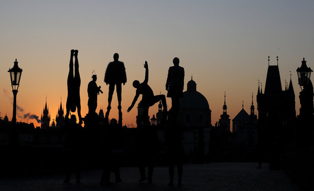 Street artists are silhouetted against the rising sun as they perform on the near empty Charles Bridge in Prague, Czech Republic, Thursday, April 2, 2020. The Czech Republic's government has approved further dramatic measures to try and stem the spread of the novel coronavirus called COVID-19. (Photo by Petr David Josek/AP Photo)