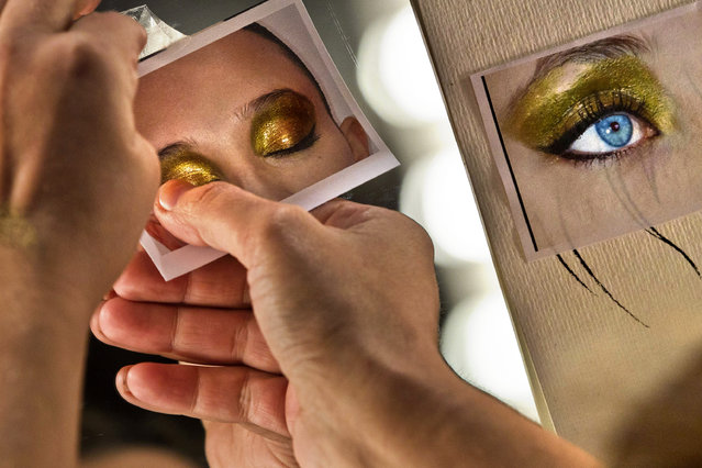 A model's make up picture is stuck to a mirror backstage during the Autumn/Winter Madrid's Mercedes Benz Fashion Week, in Madrid, Wednesday, February 1, 2012. (Photo by Daniel Ochoa de Olza/AP Photo)