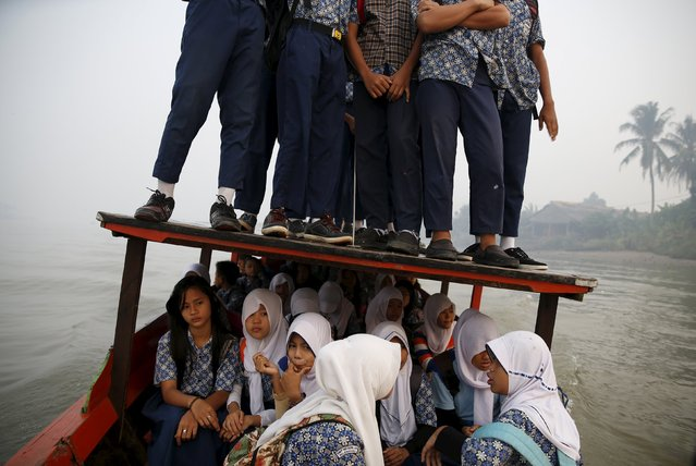 Students stand on the roof of a wooden boat as haze blankets the Musi River while they travel to school in Palembang, on Indonesia's Sumatra island, September 10, 2015. (Photo by Reuters/Beawiharta)
