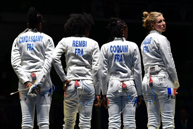 France's Marie-Florence Candassamy, Lauren Rembi, Josephine Jacques-Andre-Coquin, and Auriane Mallo (from left to right) stand together before the women's team epee classification 5-8 bout against the US as part of the fencing event, August 11, 2016. (Photo by Fabrice Coffrini/AFP Photo)