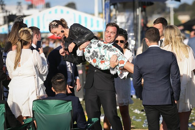A reveller picks up a woman on 2017 Derby Day at Flemington Racecourse on November 4, 2017 in Melbourne, Australia. (Photo by Splash News and Pictures)