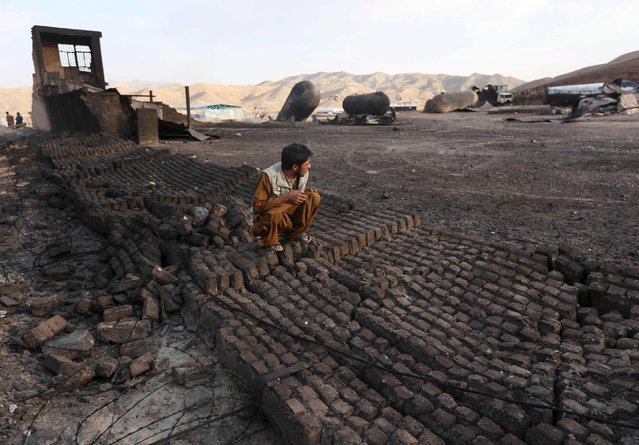 A villager inspects the site of a gas explosion in Herat province, Afghanistan, August 25, 2015. A series of large explosions at a gas terminal on the edge of the western Afghan city of Herat late on Monday killed 10 children and an adult living in a camp for people displaced by war. (Photo by Mohammad Shoib/Reuters)