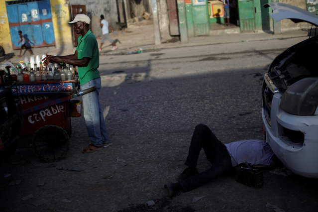 A man prepares a sorbet as another one fixes a car in a street of Port-au-Prince, Haiti, July 15, 2016. (Photo by Andres Martinez Casares/Reuters)