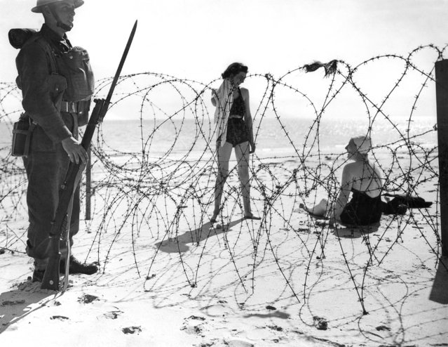 Two female holidaymakers relax on an unidentified beach of England, September 21, 1940, as a soldier, eyes straight ahead, stands guard at a barrier built as a defense against possible invasion by Germany. (Photo by AP Photo)