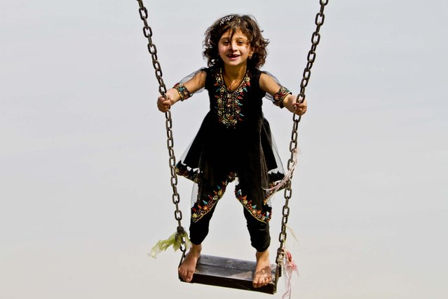 A girl enjoys a swing in an amusement park in Jalalabad, Afghanistan, November 12, 2012. (Photo by Rahmat Gul/Assoiciated Press)