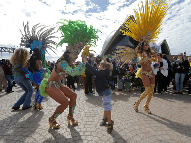 A Brazilian dancer high-fives with a boy from the audience during an official welcome home for Australia's Olympic athletes back from Rio at the Sydney Opera House in Australia, August 29, 2016. (Photo by Jason Reed/Reuters)